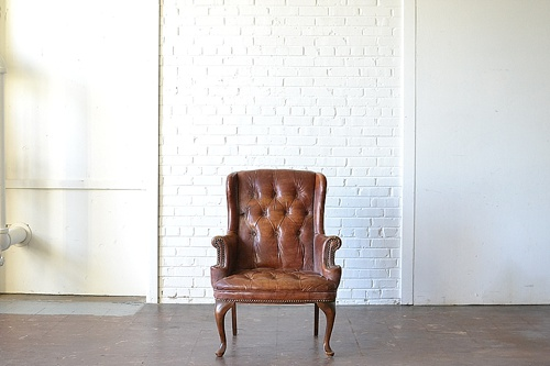 The Dalls leather upholstered chair available for rent by Paisley & Jade