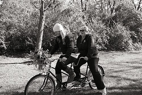 Co-Captains of Paisley & Jade, Morgan and Perkins, pedal on P&J's vintage Tandem Bicycle.