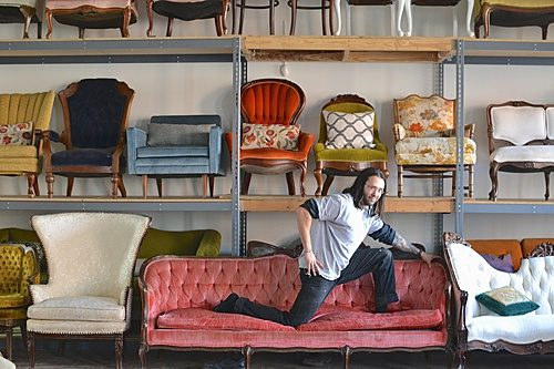 Paisley & Jade's Warehouse Manager poses for the photographer on a vintage upholstered couch!